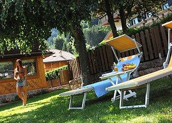 Residences a Moena. giardino attrezzato con lettini e giochi per i bambini