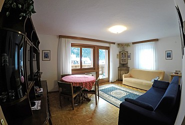 Apartment in Canazei. Living-room is spacious and bright with TV-SAT, table, sofa and an armchair.