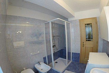 Apartment in Canazei. There are two bathrooms with windows. The big one holds utilities, wash-basin with mirror, bathtub, washing machine and phon.