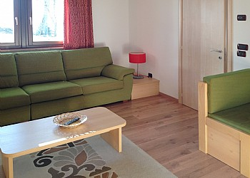 Apartment in Soraga. The living-room with two overview windows. The wooden floor is particolary appreciated.
